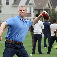 (Boston, MA -- 8/23/15)  Gov. Charlie Baker tosses a football during the Boston Mayor's Cup at Roberts Playground in Dorchester, Sunday, August 23, 2015. Baker's wife, Lauren, is seen at right. Staff photo by Angela Rowlings