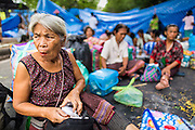 """11 MAY 2013 - BANGKOK, THAILAND:   Women from the Thai countryside sit in the road in front of Government House. Several hundred small scale family farmers camped out """"Government House"""" (the office of the Prime Minister) in Bangkok to Thai Prime Minister Yingluck Shinawatra to deliver on her promises to improve the situation of family farmers. The People's Movement for a Just Society (P-move) is a network organization which aims strengthen the voices of different, but related causes working to bring justice for marginalized groups in Thailand, including land rights for small-scale farmers, citizenship for stateless persons, fair compensation for communities forced to relocate to accommodate large scale state projects, and housing solutions for urban slum dwellers, among others.   PHOTO BY JACK KURTZ"""