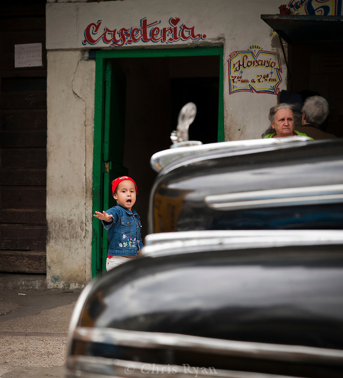 Child framed by classic car in Havana, Cuba