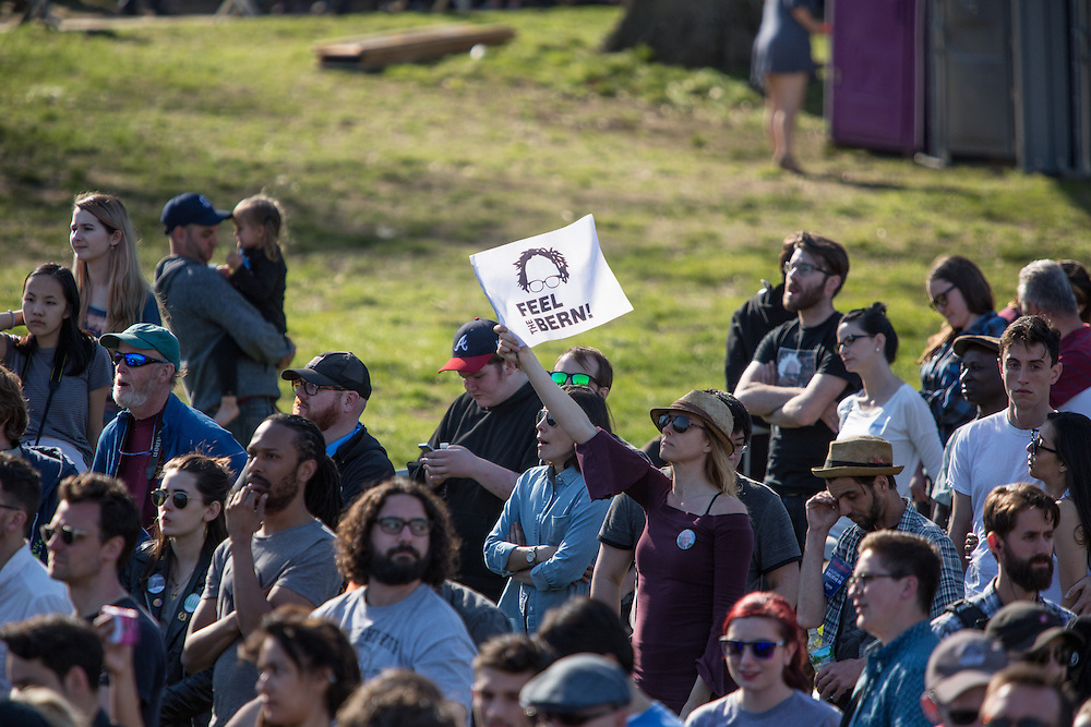 """Brooklyn, NY - 17 April 2016. A supporter in the crowd waves a banner reading """"Feel the Bern"""", one of his campaign slogans. Vermont Senator Bernie Sanders, who is running as a Democrat in the U.S. Presidential primary elections, held a campaign """"get out the  vote"""" rally in Brooklyn's Prospect Park."""