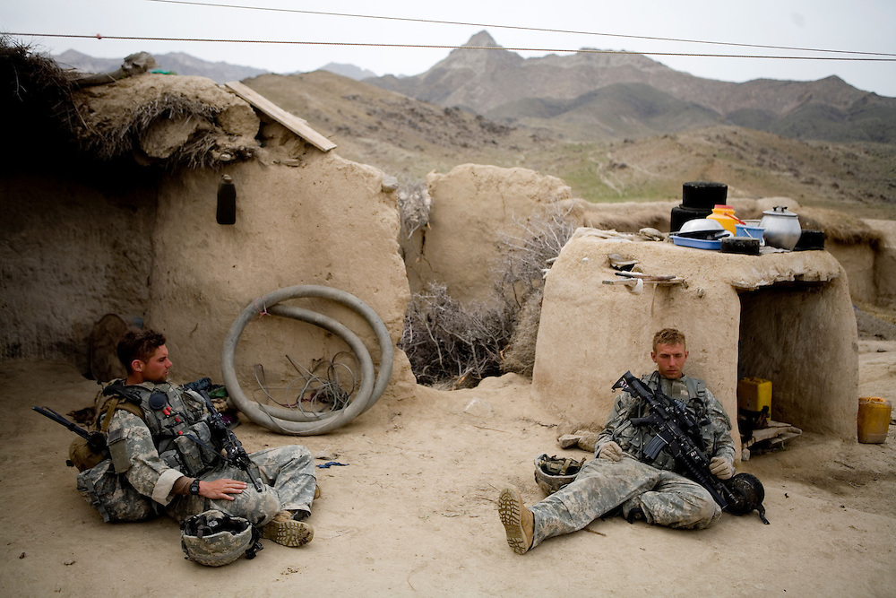 Sargeant Ryan Doolittle, left, and Specialist William White of the 82nd Airborne, 1/508 Parachute Infantry Regiment, Alpha Company, Third Platoon, take a break from searching the remote moutain village of Kshahah Lakhchack in Kandahar province, Afghanistan on Monday, March 26, 2007.