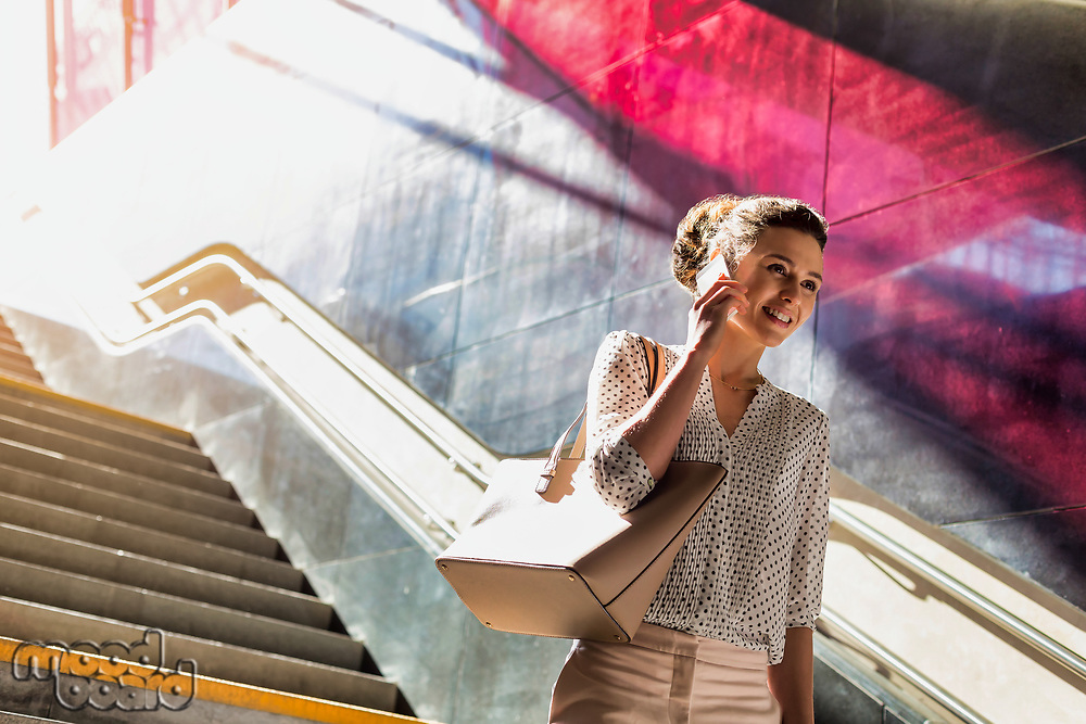 Portrait of young attractive businesswoman talking on smartphone while walking downstairs