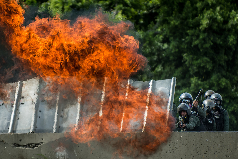 CARACAS, VENEZUELA - MAY 24, 2017: A molotov cocktail thrown by anti-government protesters explodes over National Guard soldiers firing tear gas, rubber bullets and buckshot  at protesters. The streets of Caracas and other cities across Venezuela have been filled with tens of thousands of demonstrators for nearly 100 days of massive protests, held since April 1st. Protesters are enraged at the government for becoming an increasingly repressive, authoritarian regime that has delayed elections, used armed government loyalist to threaten dissidents, called for the Constitution to be re-written to favor them, jailed and tortured protesters and members of the political opposition, and whose corruption and failed economic policy has caused the current economic crisis that has led to widespread food and medicine shortages across the country.  Independent local media report nearly 100 people have been killed during protests and protest-related riots and looting.  The government currently only officially reports 75 deaths.  Over 2,000 people have been injured, and over 3,000 protesters have been detained by authorities.  PHOTO: Meridith Kohut