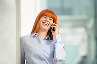 Cheerful businesswoman talking on cell phone in office