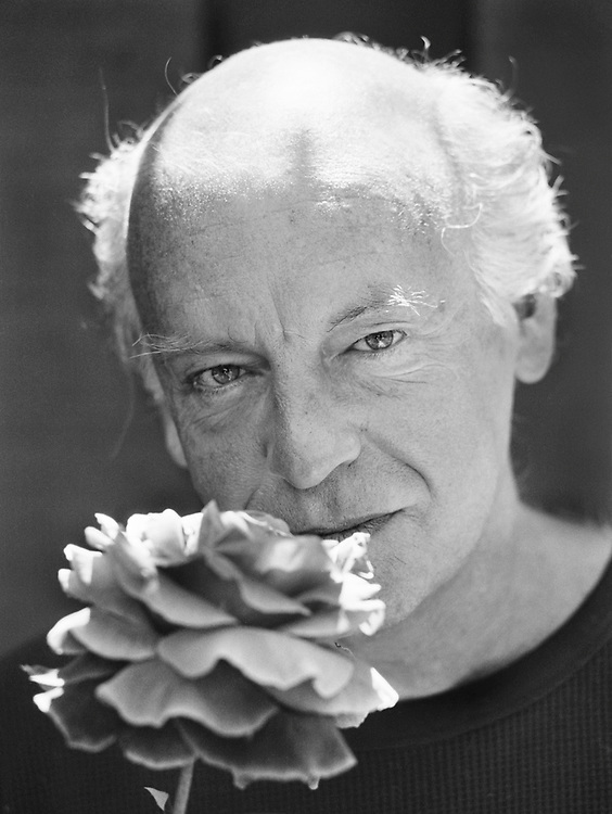 close framed portrait of Galeano with a rose, and an intense gaze