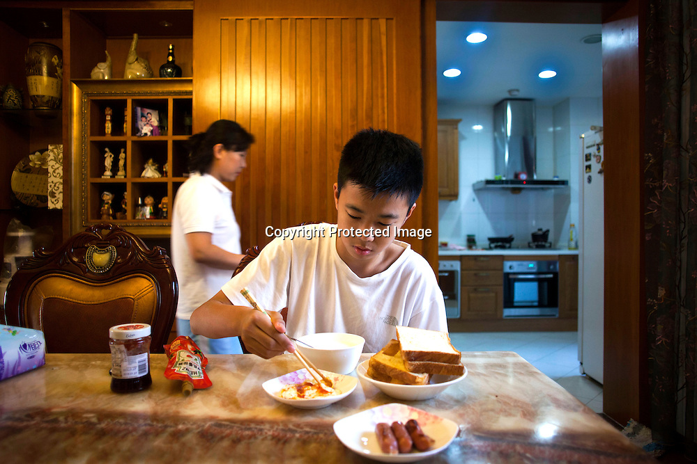 BEIJING, OCT.18, 2014 : Song Yonglin,14, eats breakfast prepared by his mother ( L)  before he heads to school. he  spends every weekend taking extra school lessons in order to improve his scores which cost his parents about 4-5000 Yuan/month. He would like to switch to the International school in Beijing  and study economics later on in the US.