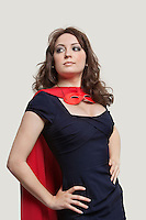 Beautiful woman in superhero costume over gray background