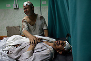 Palestinians help medical workers tend to their wounded in the emergency room at the   Kamal Adwan hospital in northern Gaza where many of the wounded and dead were taken after  several Israeli tank shells slammed into a crowded U.N. school used as shelter for refugees in the Gaza war early on Wednesday July 30,2014 , killing at least 15 people and wounding 90, a Palestinian health official and a U.N. official said. Ten donkeys were killed  and many lay dying .The deadly strike came a day after Israel unleashed its heaviest air and artillery assault in the bloodiest day of the three-week Gaza war, destroying key symbols of Hamas control, shutting down the territory's only power plant and leaving at least 128 Palestinians dead. (Photo by Heidi Levine/Sipa Pressl).