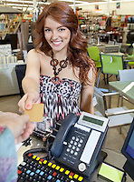 Portrait of a happy young woman paying through credit card