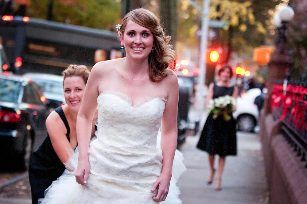 Erin's bridesmaids help her down the street before her Catholic wedding in Brooklyn, New York.