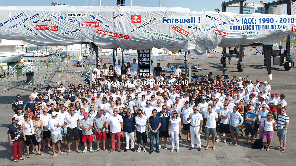Teams, volunteers and organisers assemble for a group photo under a wrapped up IACC boat. Louis Vuitton Trophy Dubai. 27/11/2010