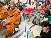 11 JULY 2011 - BANGKOK, THAILAND:    Buddhist monks wait for their trains at Hua Lamphong station in Bangkok. Hua Lamphong Grand Central Railway Station, officially known as the Bangkok Grand Central Terminal Railway Station, is the main railway station in Bangkok, Thailand. It is located in the center of the city in Pathum Wan District, and is operated by the State Railway of Thailand. The station was opened on 25 June 1916, after six years' construction. The station was built in an Italian Neo-Renaissance style, with decorated wooden roofs and stained glass windows. The architecture is attributed to Turin-born Mario Tamagno, who, with countryman Annibale Rigotti made a mark on early 20th century public building in Bangkok. The pair also designed Bang Khun Prom Palace (1906), Ananda Samakhom Throne Hall in The Royal Plaza (1907-15) and Suan Kularb Residential Hall and Throne Hall in Dusit Garden, among other buildings..There are 14 platforms and 26 ticket booths. Hua Lamphong serves over 130 trains and approximately 60,000 passengers each day. Thailand has the most advanced rail system in Southeast Asia and trains from Hua Lamphong serve all corners of the Kingdom.      PHOTO BY JACK KURTZ