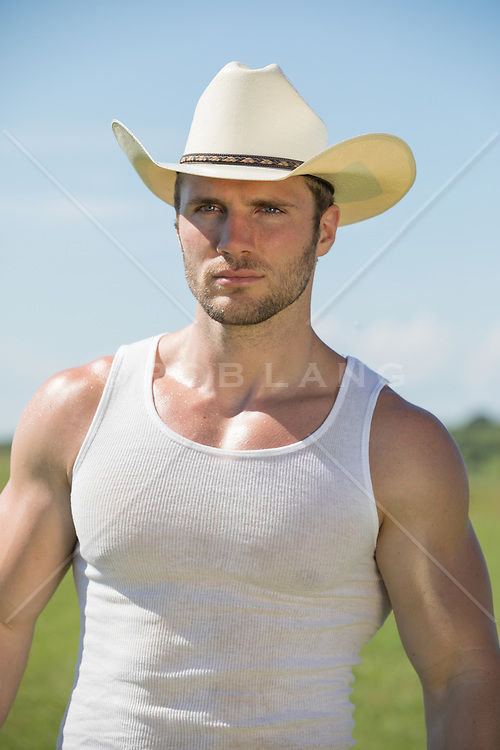 portrait of a cowboy with blue eyes in a tank top