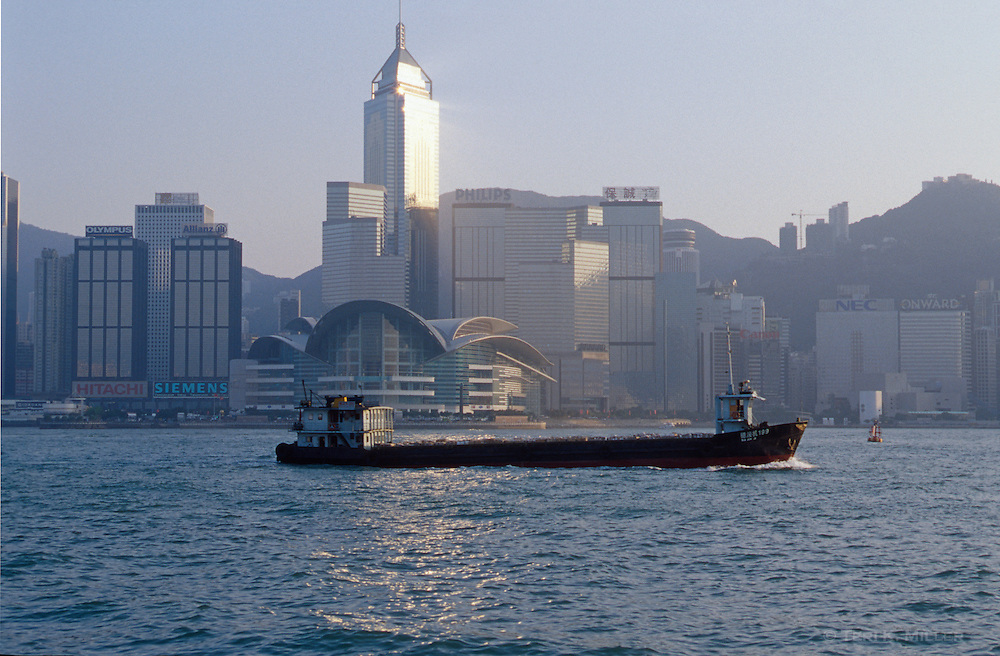 A ship carries freight in Victoria Harbour in front of the city skyline, Hong Kong, China.