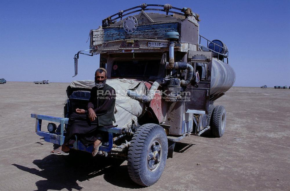 Grenze/Herat, AFG, Afghanistan, 26.09.2002: Gesichter des freien Afghanistan.Ali Mohammad, aus Herat, wartet mit seinem Tankwagen am Grenzuebergang zum Iran auf seine Ladung. Aufgrund des katastrophalen Strassenzustandes von der iranischen Grenze bis Herat werden alle Waren nur bis zur Grenze transportiert und dann von lokalen Transporteuren uebernommen. Die Weiterfahrt dauert dann meistens zwischen 3 und 7 Tagen, je nachdem ob die LKWs durchhalten. Obwohl diese Hauptstrasse von Landminen geraeumt wurde passiert es dennoch immer mal wieder das Fahrzeuge auf Landminen auffahren...© www.photoguerilla.com/Robert W. Kranz..Afghanistan, Kabul, ISAF, Enduring Freedom, Hoffnung, LKW, Tankwagen, iranische Grenze, Rueckkehrer, Afghane, Wiederaufbau, Herat, Portrait, Afghane, Tayban