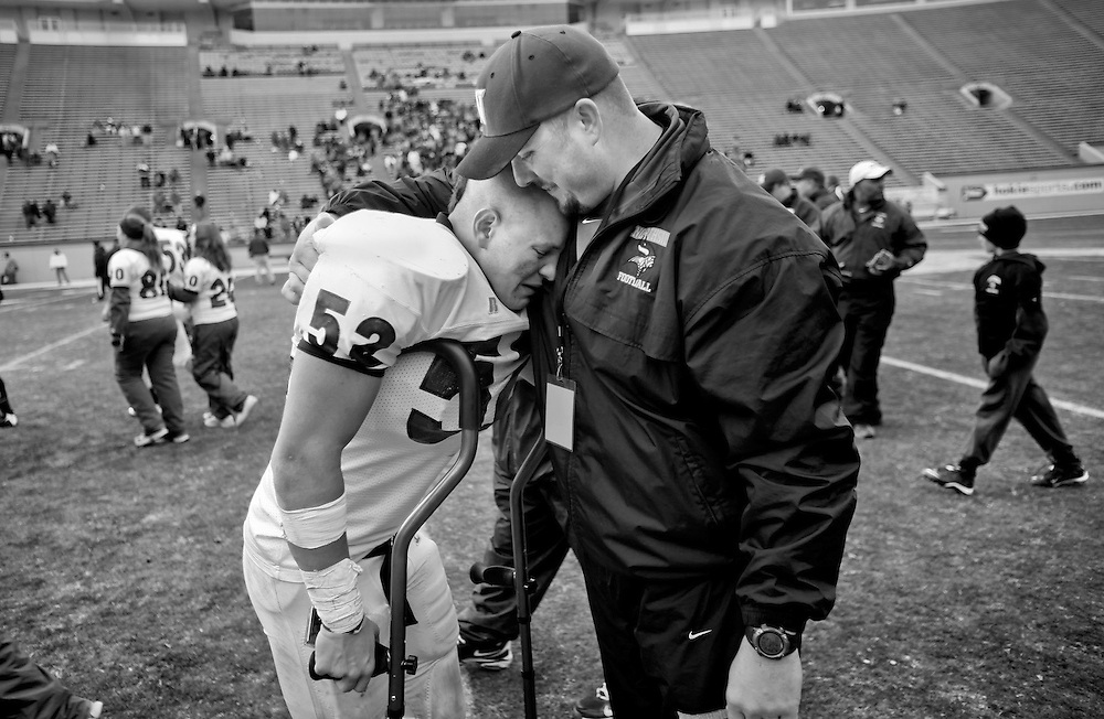 047-State Championship<br /> Northside High School football head football coach, Burt Torrence (right) hugs player, Matt Sandoval (left, #52) after the Region III State High School Football Championship game against Bruton High School Saturday in Blacksburg. Northside defeated Bruton 20-17 to win the first football state championship in school history.