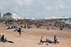 © Licensed to London News Pictures. 25/05/2014. Brighton, UK. Thousands of people are sunbathing and relaxing on the beach. The May Bank Holiday Sunday has attracted thousands of people to visit the seaside resort and take to the beach.  Photo credit : Hugo Michiels/LNP