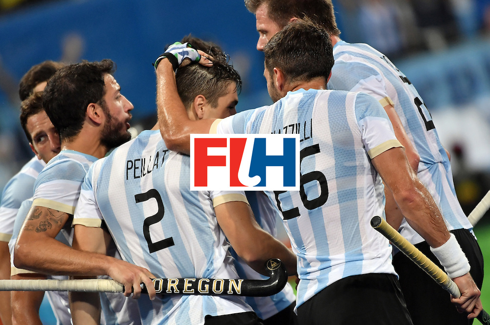 Argentina's Gonzalo Peillat (C) is congratulated by teammates after scoring their third goal during the men's Gold medal field hockey Belgium vs Argentina match of the Rio 2016 Olympics Games at the Olympic Hockey Centre in Rio de Janeiro on August 18, 2016. / AFP / Pascal GUYOT        (Photo credit should read PASCAL GUYOT/AFP/Getty Images)