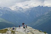 Group of hikers posing for photos at viewpoint on Abbott Ridge. Selkirk Mountains Glacier National Park British Columbia