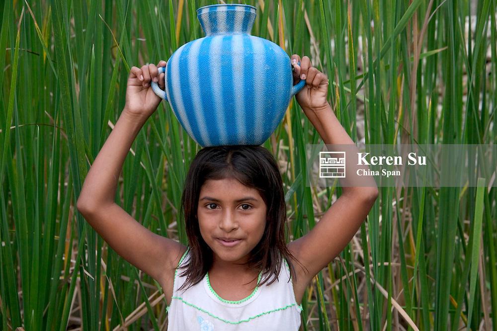 Little girl with jar on head in farmland, Remate, Guatemala