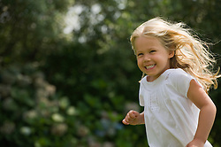 Young blonde girl running with a big smile