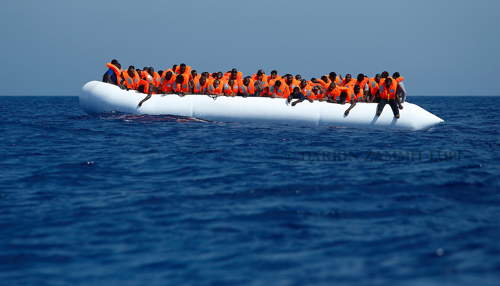 Migrants on a rubber dinghy wait to be rescued by the Migrant Offshore Aid Station (MOAS) ship MV Phoenix some 20 miles (32 kilometres) off the coast of Libya, August 3, 2015.  118 migrants were rescued from a rubber dinghy off Libya on Monday morning . The Phoenix, manned by personnel from international non-governmental organisations Medecins san Frontiere (MSF) and MOAS, is the first privately funded vessel to operate in the Mediterranean.<br /> REUTERS/Darrin Zammit Lupi <br /> MALTA OUT. NO COMMERCIAL OR EDITORIAL SALES IN MALTA