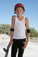 Teenage boy (13-15) with skateboard at skateboard park portrait