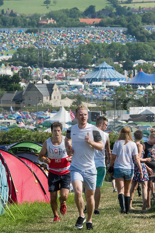 © Licensed to London News Pictures. 25/06/2015. Pilton, UK. Festival atmosphere at Glastonbury Festival 2015 on Thursday Day 2 of the festival - joggers run and down up a steep hill on a hot sunny morning.  This years headline acts include Kanye West, The Who and Florence and the Machine, the latter having been upgraded in the bill to replace original headline act Foo Fighters.   Photo credit: Richard Isaac/LNP
