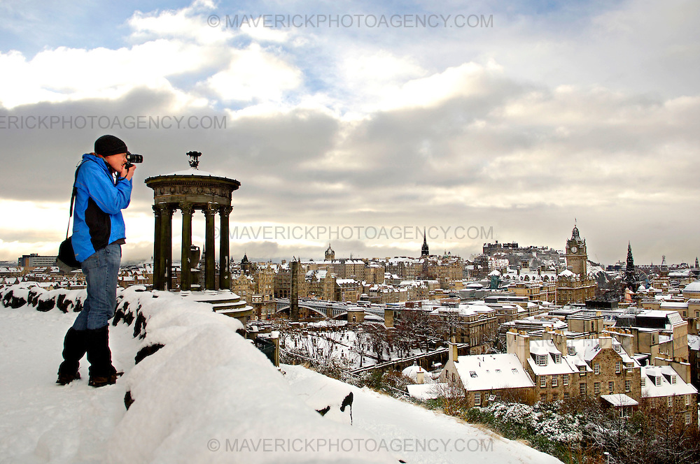 EDINBURGH, UK - 28th November 2010:  A member of the public takes a picture of Edinburgh Castle and surrounding rooftops from Calton Hill after heavy snow hit the city early on Sunday morning. ..Heavy snow has fallen across large parts of the UK, disrupting travel.  Weather warnings of heavy and drifting snow are also in place for many places across the UK...(Photograph: Richard Scott/MAVERICK)