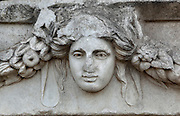 Mask and garland frieze from the Portico of Tiberius on the Southern portico of the Agora, 1st century AD, Aphrodisias, Aydin, Turkey. The Sculpture School at Aphrodisias was an important producer of carved marble sarcophagi and friezes from the 1st century BC until the 6th century AD. The Portico of Tiberius was built under the reign of Tiberius and has many examples of mask and garland friezes, consisting of the heads of gods, goddesses, theatrical characters, mythological figures or masks, each with a distinct facial expression, between hanging garlands of leaves, fruit and flowers. This example shows a solemn young woman. Aphrodisias was a small ancient Greek city in Caria near the modern-day town of Geyre. It was named after Aphrodite, the Greek goddess of love, who had here her unique cult image, the Aphrodite of Aphrodisias. The city suffered major earthquakes in the 4th and 7th centuries which destroyed most of the ancient structures. Picture by Manuel Cohen