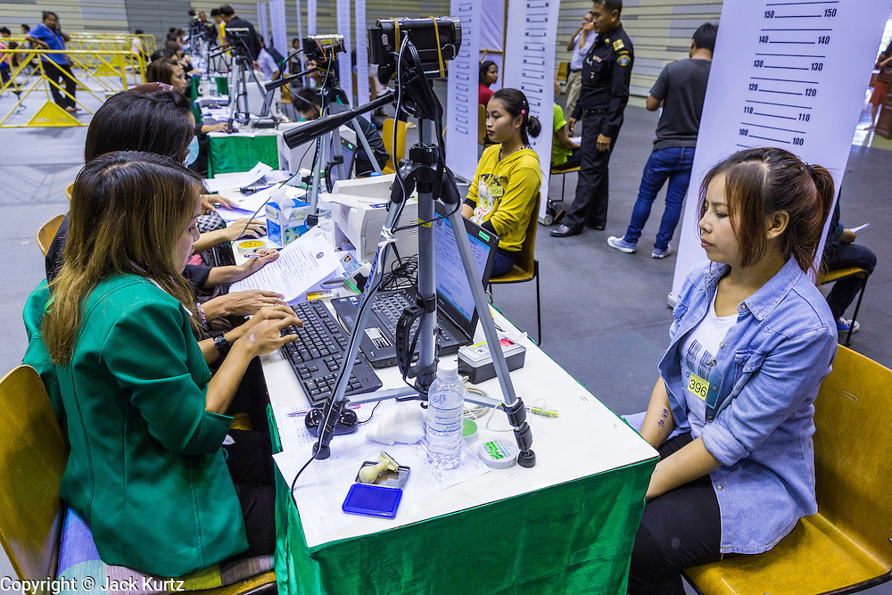 "17 JULY 2014 - BANGKOK, THAILAND: Thai immigration workers help undocumented Cambodian workers register for ID cards and work permits at the temporary ""one stop service center"" in the Bangkok Youth Center in central Bangkok. Thai immigration officials have opened several temporary ""one stop service centers"" in Bangkok to register undocumented immigrants and issue them temporary ID cards and work permits. The temporary centers will be open until August 14.    PHOTO BY JACK KURTZ"