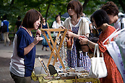 Customers look at handmade jewelry at a store in the Art Market inside  Inokashira Park in  the trendy neighborhood of Kichijoji in Musashino City,  Tokyo, Japan on 16 Sept. 2012.  Photographer: Robert Gilhooly