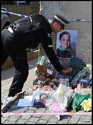 Police officers lay flowers near Tia Sharp's Grandma's house in New Addington, given to them by neighbours to pay respect to Tia Sharp, Who went missing a week ago. A body was found in Tia Sharp's Grandma's House on Friday August 10, 2012. Saturday August 11, 2012. Photo by Andrew Parsons/i-Images..All Rights Reserved ©Andrew Parsons/i-Images.See Instructions