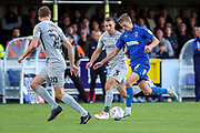 AFC Wimbledon attacker Marcus Forss (15) dribbling and taking on Portsmouth defender Sean Raggett (20) and Portsmouth defender Lee Brown (3) during the EFL Sky Bet League 1 match between AFC Wimbledon and Portsmouth at the Cherry Red Records Stadium, Kingston, England on 19 October 2019.