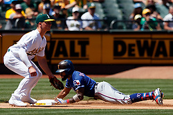 OAKLAND, CA - JULY 28:  Delino DeShields #3 of the Texas Rangers slides into third base for a triple in front of Matt Chapman #26 of the Oakland Athletics during the fifth inning at the RingCentral Coliseum on July 28, 2019 in Oakland, California. The Oakland Athletics defeated the Texas Rangers 6-5. (Photo by Jason O. Watson/Getty Images) *** Local Caption *** Delino DeShields; Matt Chapman