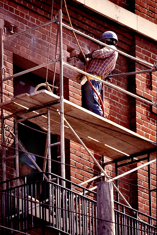 worker removin bricks on scaffold above fire escape on historic brannen st, San Francisco building