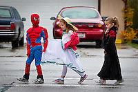 Southern belle Ellee Rebeck and a cloaked Autumn Goncalves walk behind Spiderman on their way to Bestland Retirement Community with their kindergarten class from Borah Elementary during the school's Halloween parade Friday.