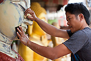"05 JULY 2011 - BANGKOK, THAILAND:   A man paints a statue of a Buddha on Bamrung Muang Street in Bangkok. Thanon Bamrung Muang (Thanon is Thai for Road or Street) is Bangkok's ""Street of Many Buddhas."" Like many ancient cities, Bangkok was once a city of artisan's neighborhoods and Bamrung Muang Road, near Bangkok's present day city hall, was once the street where all the country's Buddha statues were made. Now they made in factories on the edge of Bangkok, but Bamrung Muang Road is still where the statues are sold. Once an elephant trail, it was one of the first streets paved in Bangkok, it is the largest center of Buddhist supplies in Thailand. Not just statues but also monk's robes, candles, alms bowls, and pre-configured alms baskets are for sale along both sides of the street.          PHOTO BY JACK KURTZ"