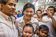 17 FEBRUARY 2013 - BANGKOK, THAILAND:   Thai Prime Minister YINGLUCK SHINAWATRA talks to voters while campaigning for Pongsapat Pongchareon in Bangkok Sunday. Pol General Pongsapat Pongcharoen, a former deputy national police chief who also served as secretary-general of the Narcotics Control Board is the Pheu Thai Party candidate in the upcoming Bangkok governor's election. (He resigned from the police force to run for Governor.) Former Prime Minister Thaksin Shinawatra reportedly recruited Pongsapat. Most of Thailand's reputable polls have reported that Pongsapat is leading in the race and likely to defeat Sukhumbhand Paribatra, the Thai Democrats' candidate and incumbent. The loss of Bangkok would be a serious blow to the Democrats, whose base is the Bangkok area.    PHOTO BY JACK KURTZ