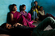(left to right) Ravi, 14, Sanjita, 41, Poonam, 12, Arti, 18, and Jyoti, 13, are sitting together watching television inside their newly built home in Oriya Basti, a water-affected urban colony of Bhopal, Madhya Pradesh, India, near the abandoned Union Carbide (now DOW Chemical) industrial complex.