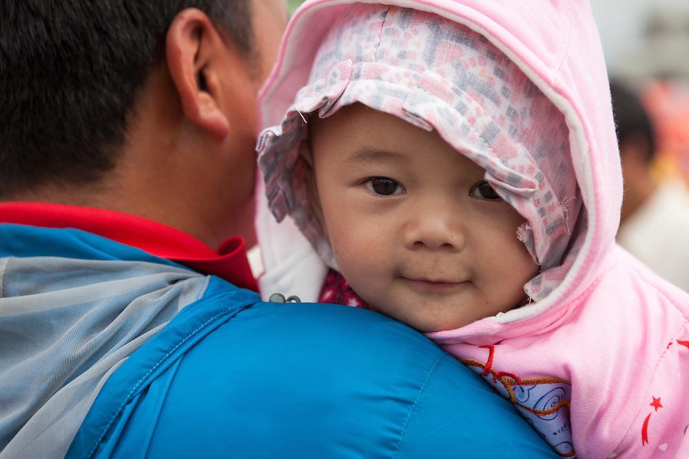 Baby op de schouder van haar vader in een tentenkamp in de buitenwijk Boudhanath.