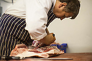 A butcher cuts a side of beef for preparation for sale. A butcher's shop and slaughterhouse in Yorkshire, England