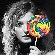 Selective color photo of model with lollipop.