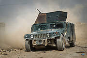 An Emergency Response Unit humvee is seen driving through the dusty streets of the western Mosul 17 Tammuz neighbourhood on May 19, 2017.