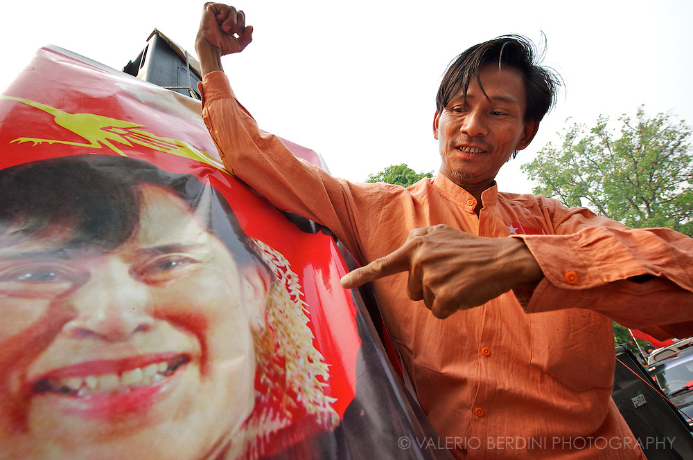A man with the traditional orange shirt of the NLD supporters, proudly poses next to a big picture of Aung San Suu Kyi on a Mandalay parade. Myanmar. 2012