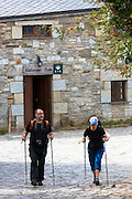 Pilgrims setting off from Habitaciones Frade to continue the Camino de Santiago pilgrim route at Triacastela in Galicia, Spain