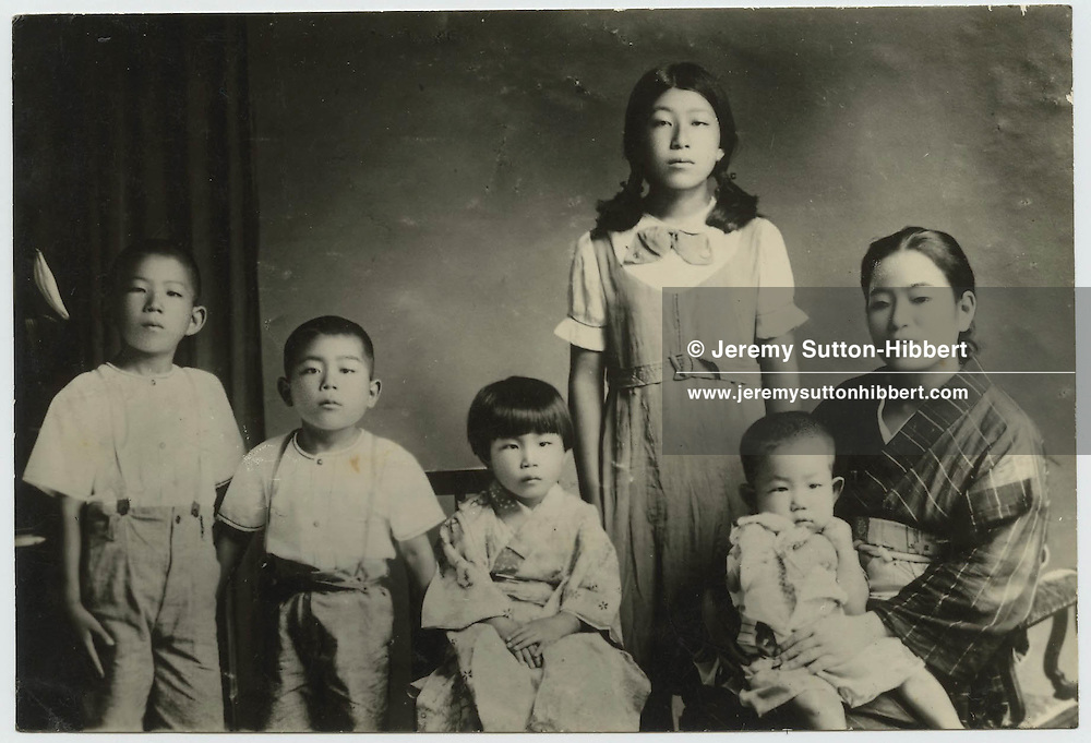 Kenzaburo Oe sits on the lap of his mother, with brothers and sisters in their home in Ehime Prefecture, Shikoku Island, Japan in 1936.    Kenzaburo Oe is now Japanese author/essayist/novelist. Born 1935, winner of 1994 Nobel Prize for Literature. Father of Hikari Oe, composer.