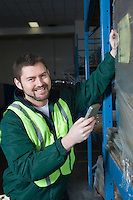 Cheerful man using calculator in factory