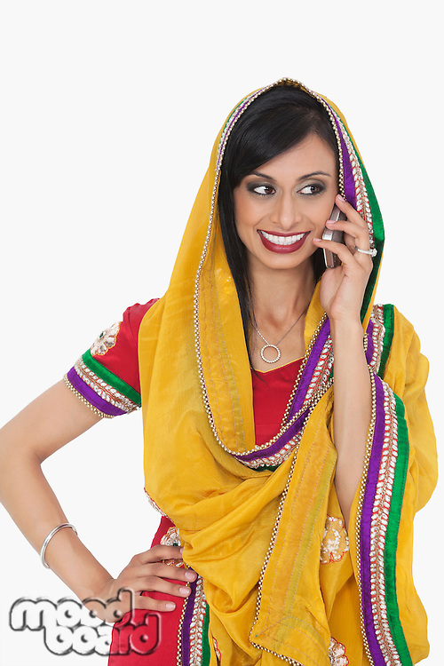 Beautiful Indian woman in traditional wear answering phone call over gray background