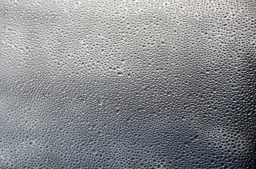 Condensation on a cold window pane from humid indoor air: winter in Maine.